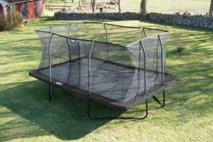 Stor rektangulär studsmatta i trädgård